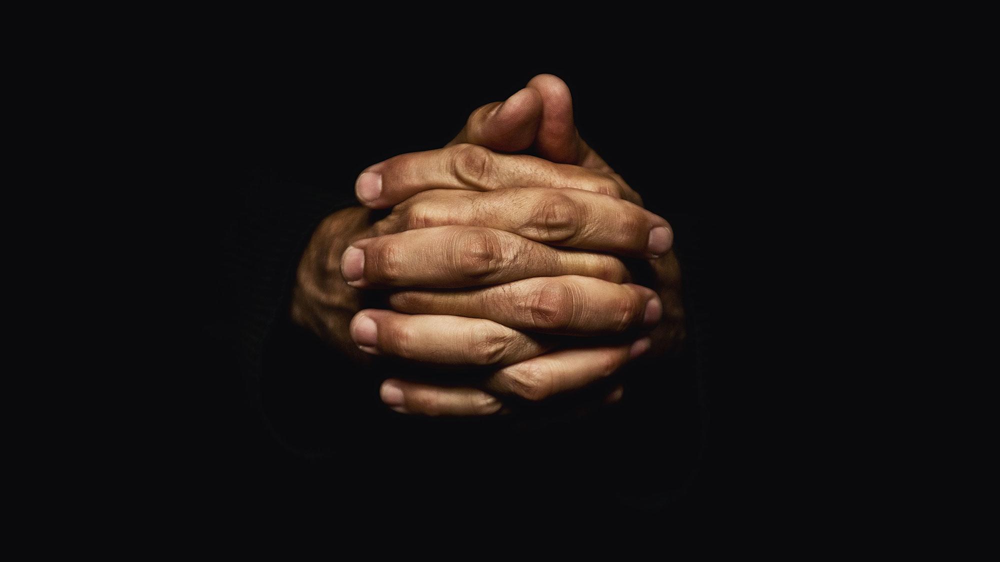 Hands crossed for prayer in the dark.