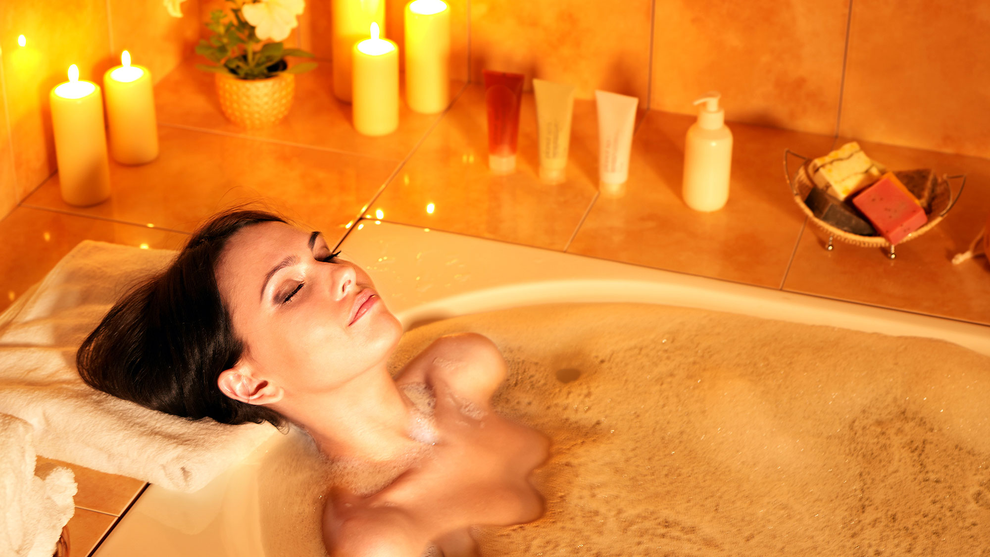 Woman taking a warm bubble bath.