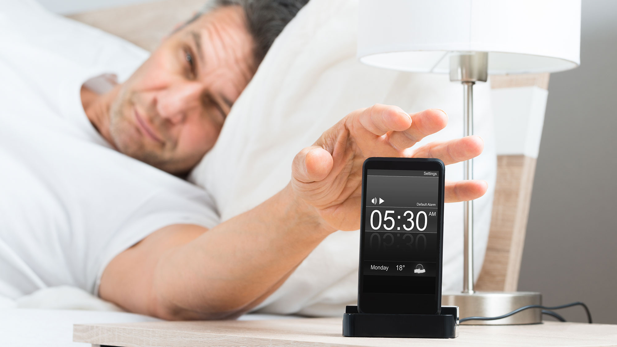 Man turning off his iPhone alarm clock.