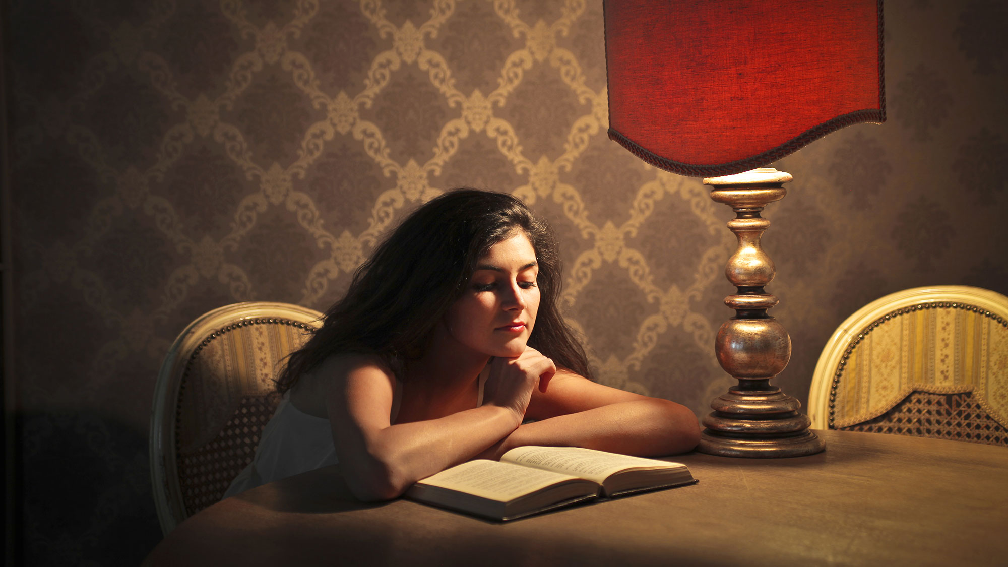 Girl reading a book late at night.