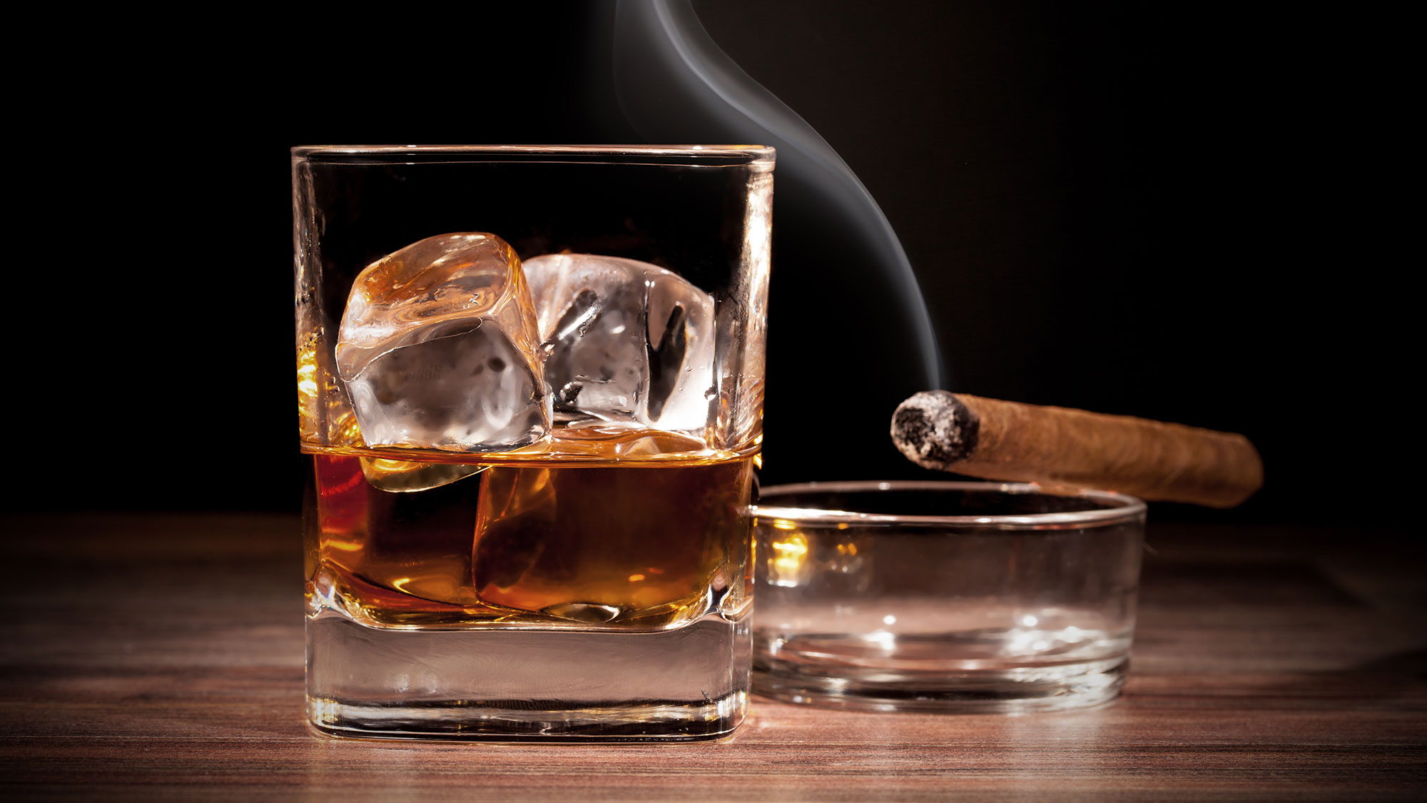 Glass of whiskey with a smoking cigar.
